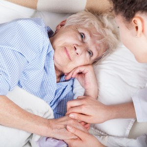 Elderly woman in bed and her caregiver