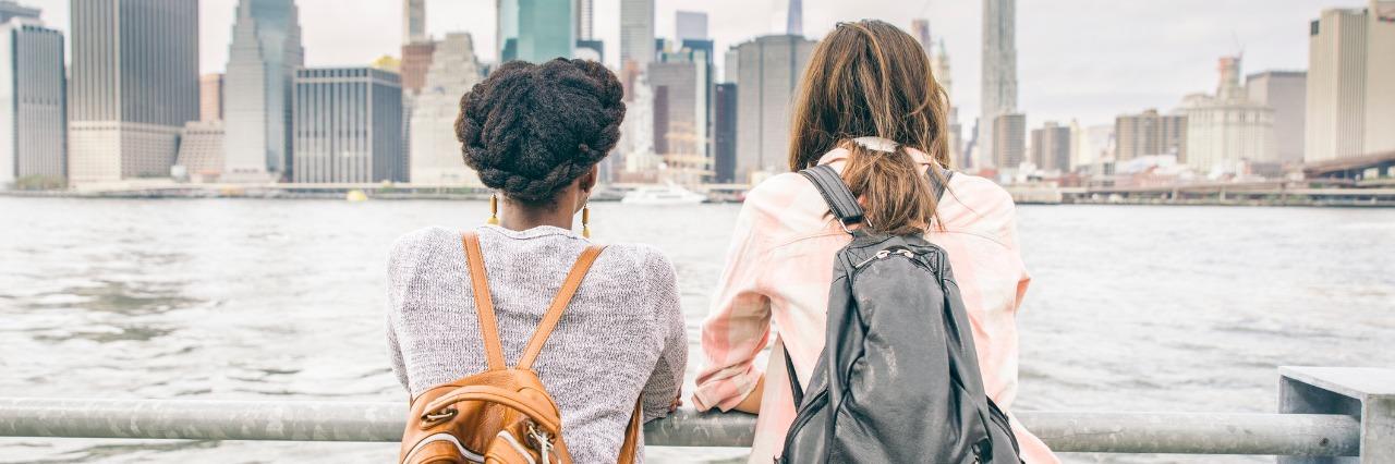 women wearing backpacks standing on bridge looking at skyline