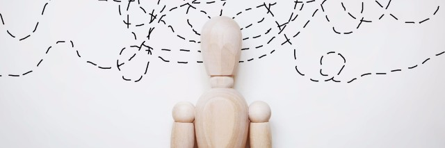 wooden human figure with lines swirling around his head