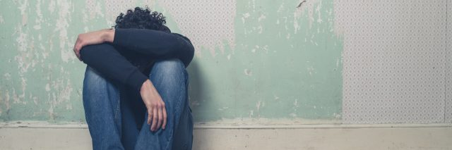 depressed young man sitting on floor in empty room with peeling wallpaper
