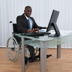 Man in a wheelchair working in an office.