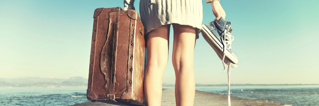 woman standing on a dock and holding her suitcase and shoes