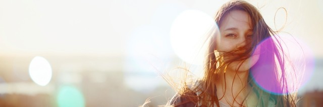 Young Woman Standing in Sunset Light, Looking at Camera. Hair Fluttering in the Wind. Selective Focus,