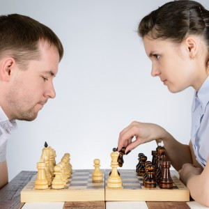 man and woman playing chess and staring at each other intently