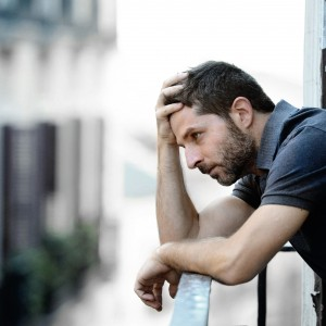 young man alone outside at house balcony terrace looking depressed