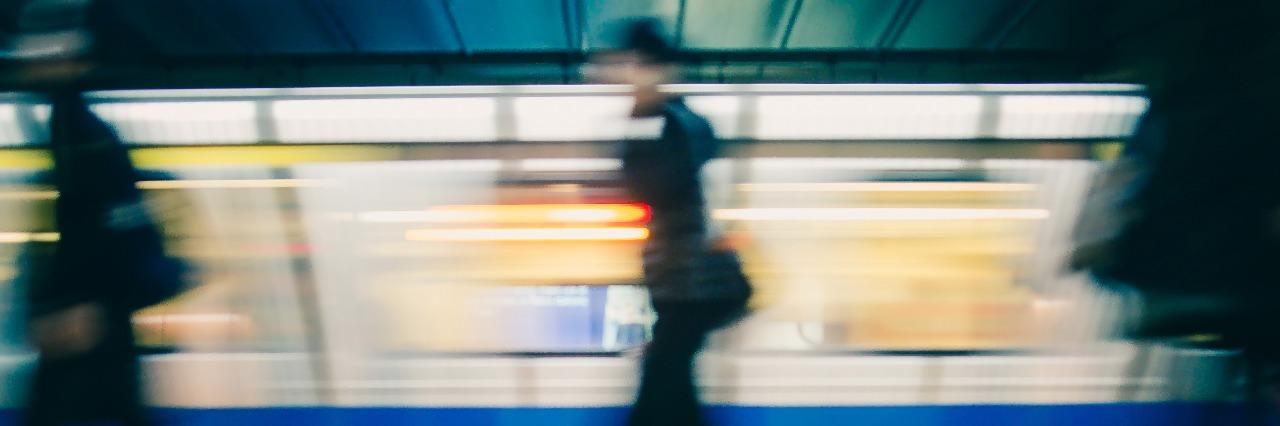 Subway train leaving station. People on platform.