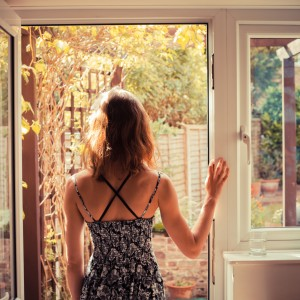 A young woman is standing in the doorway of her kitchen and is looking at the garden at sunrise