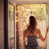 woman standing in a doorway looking outside