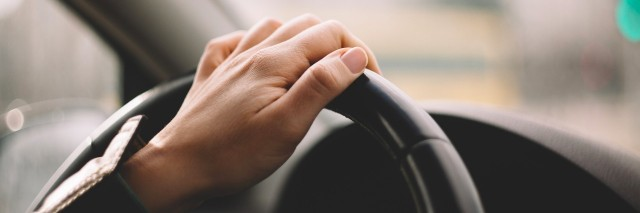 Hand on steering wheel while driving a car