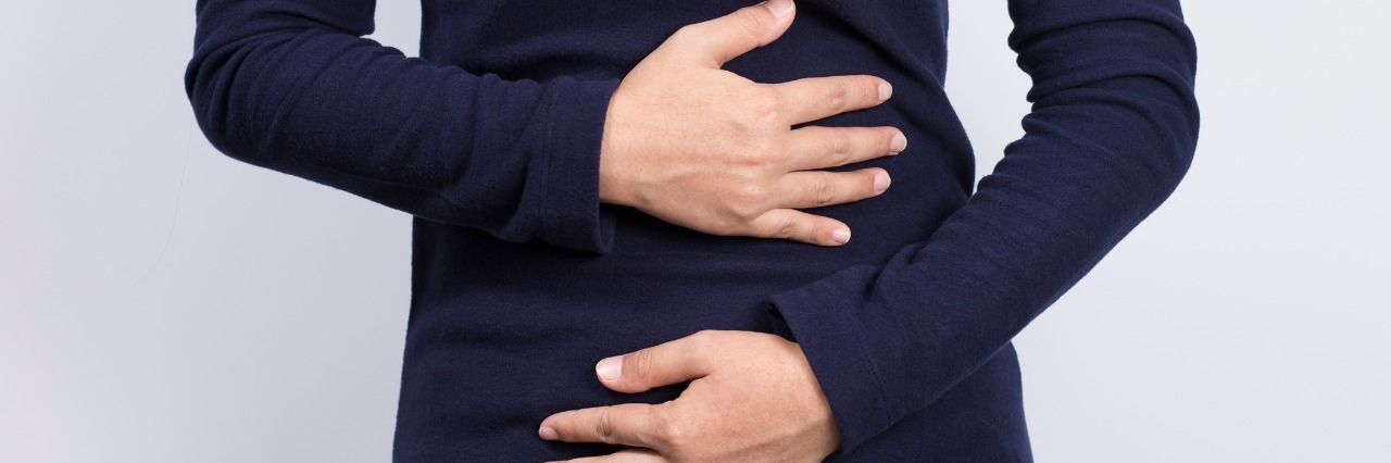 woman in dark blue shirt holding her stomach
