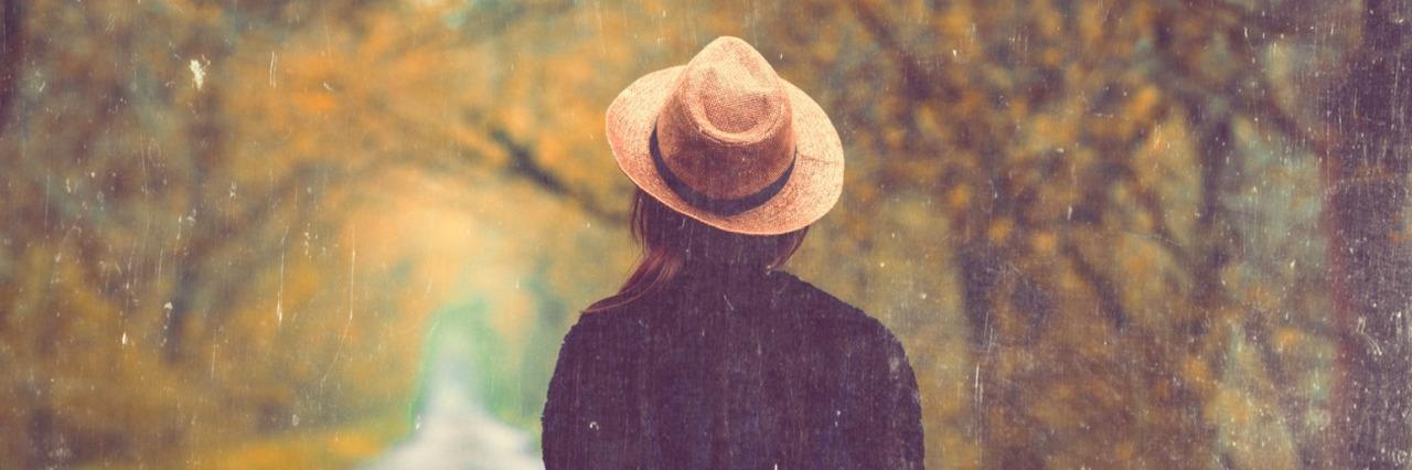 Woman wearing hat walking down tree-lined path