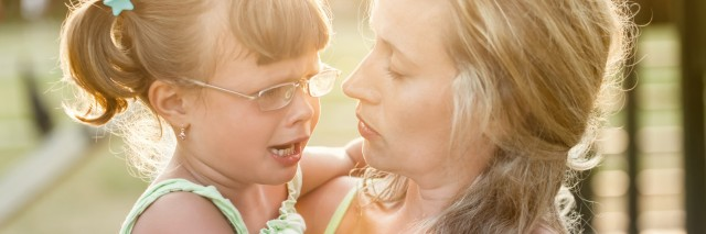 Mother comforts crying daughter outdoors ,