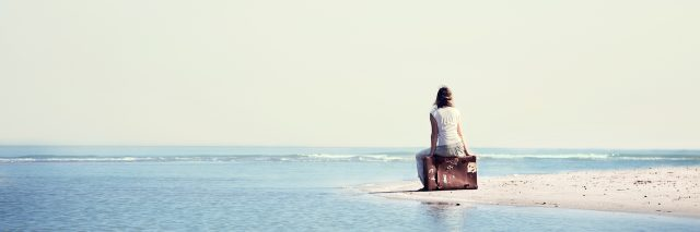 A woman sitting on a bag, looking at the ocean
