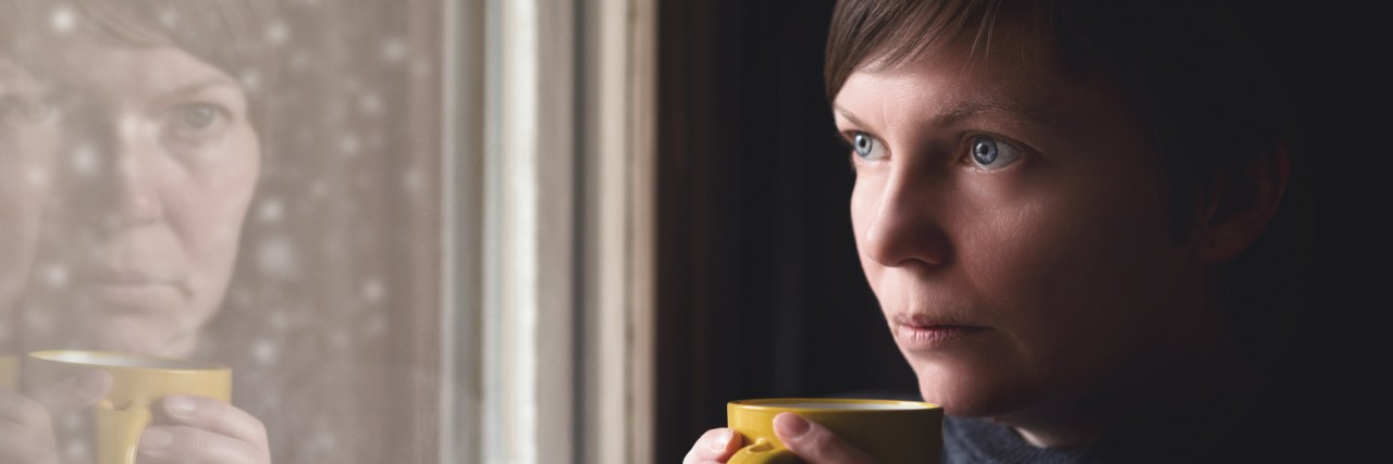 Lonesome woman drinking cup of coffee by the window of her living room