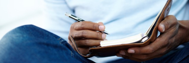 Hands of young man writing something in notepad