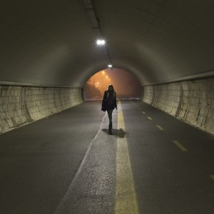 young lady walks alone trough a tunnel in the night