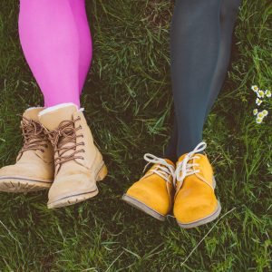 Two woman laying in the ground with colored leggings and boots