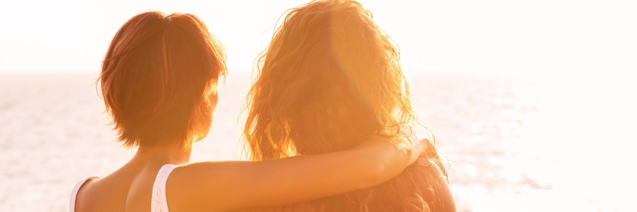 two female friends hugging and looking at sunset