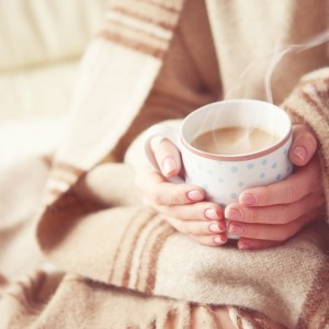 woman's hands holding warm mug of coffee. she is wrapped in a warm heavy blanket