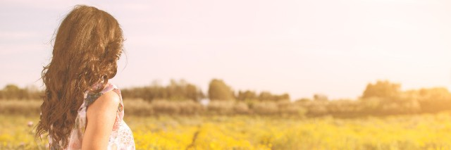 Woman sitting in a field looking at the horizon.