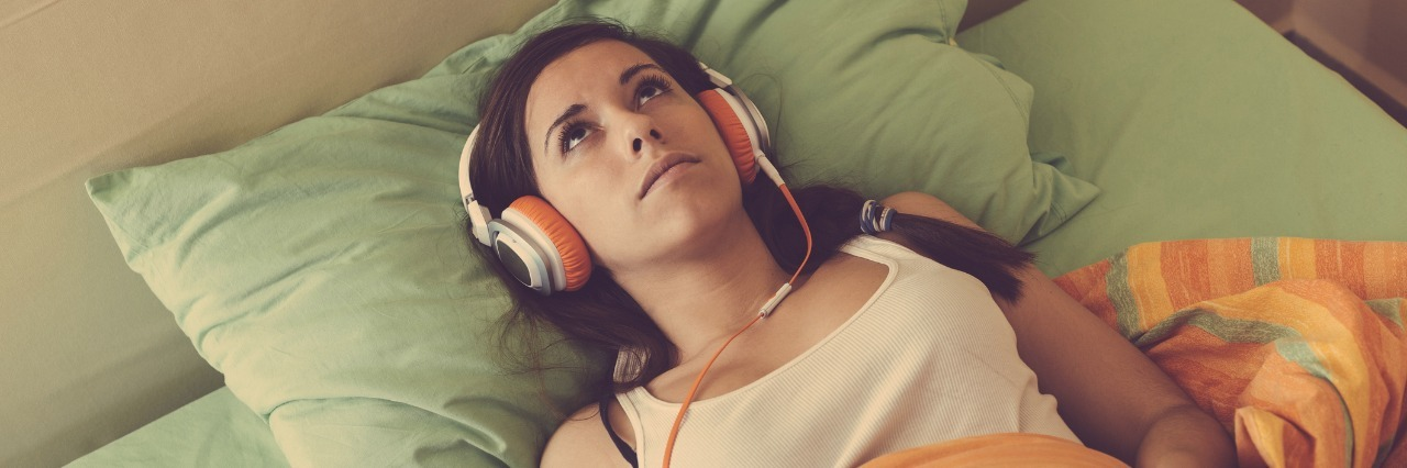 woman laying in bed listening to music