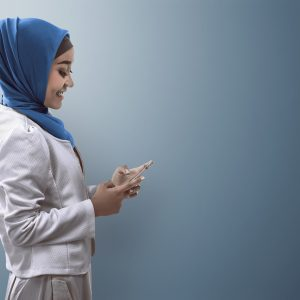 A woman waring a hijab on her phone.
