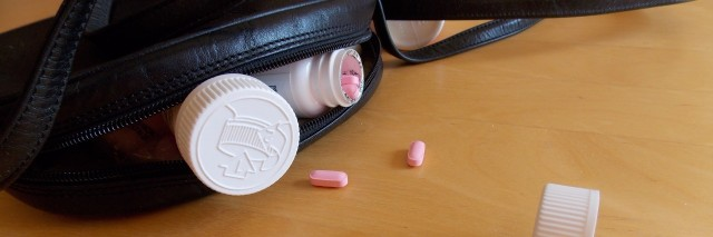 Three pill bottles, one of which is open, and red and pink pills spill out from a black handbag with a twisted strap.