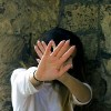woman holding her hands up in front of her face and looking away in front of stone wall