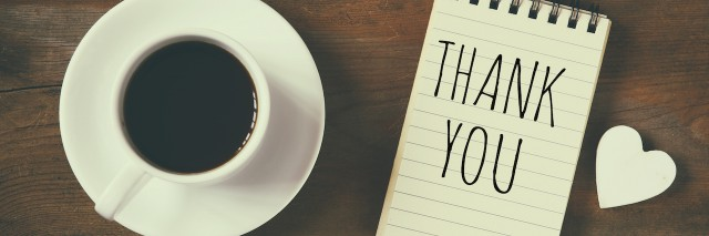 notebook that reads Thank You next to a cup of coffee