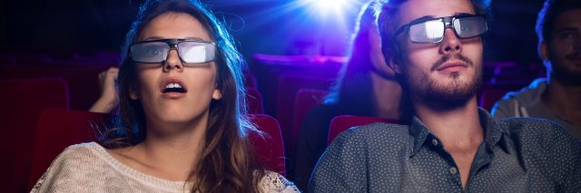 Couple watching a movie wearing 3-D glasses