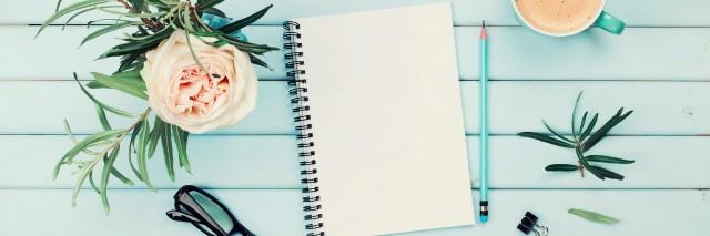 Morning coffee cup, clean notebook, pencil, eyeglasses and vintage rose flower in vase on