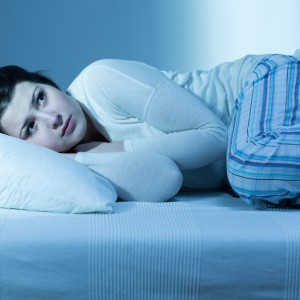 a woman lying down, looking scared in bed