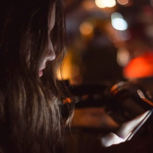 Girl using smart phone at night