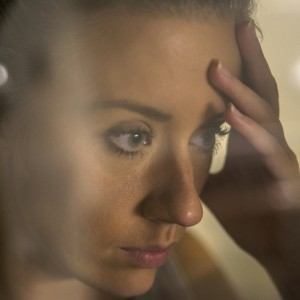 pensive woman looking through window