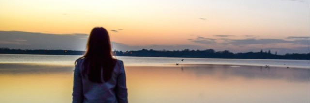 Woman standing in front of lake at sunset