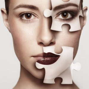 Woman with jigsaw puzzle pieces on face.