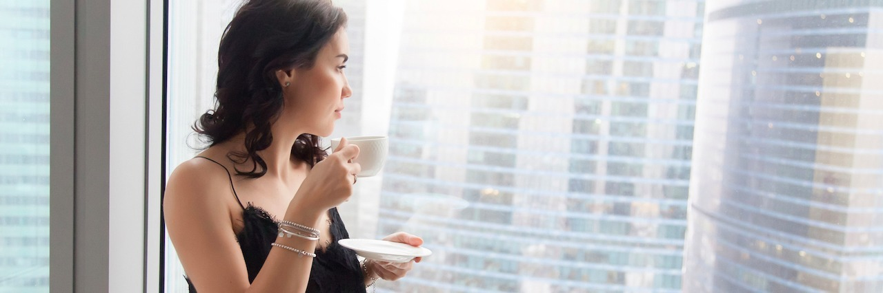 woman looking out the window, drinking tea