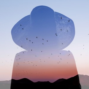 double exposure of a woman wearing a large hat and a sunset behind a mountain with birds flying in the air