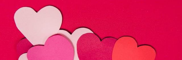 Colorful paper hearts on red paper background
