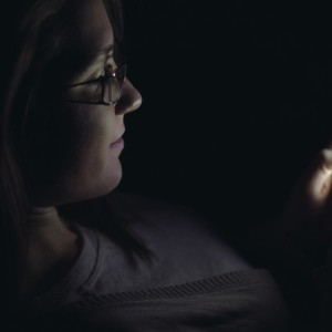 Young woman using mobile phone in dark room at night