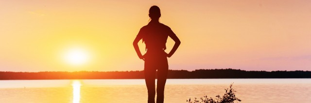 silhouette of woman standing next to lake at sunset