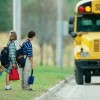 side profile of students standing in line for a school bus