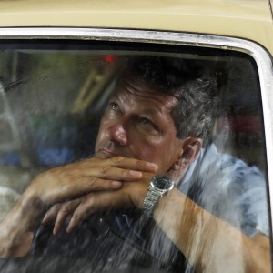 Man looks out car window
