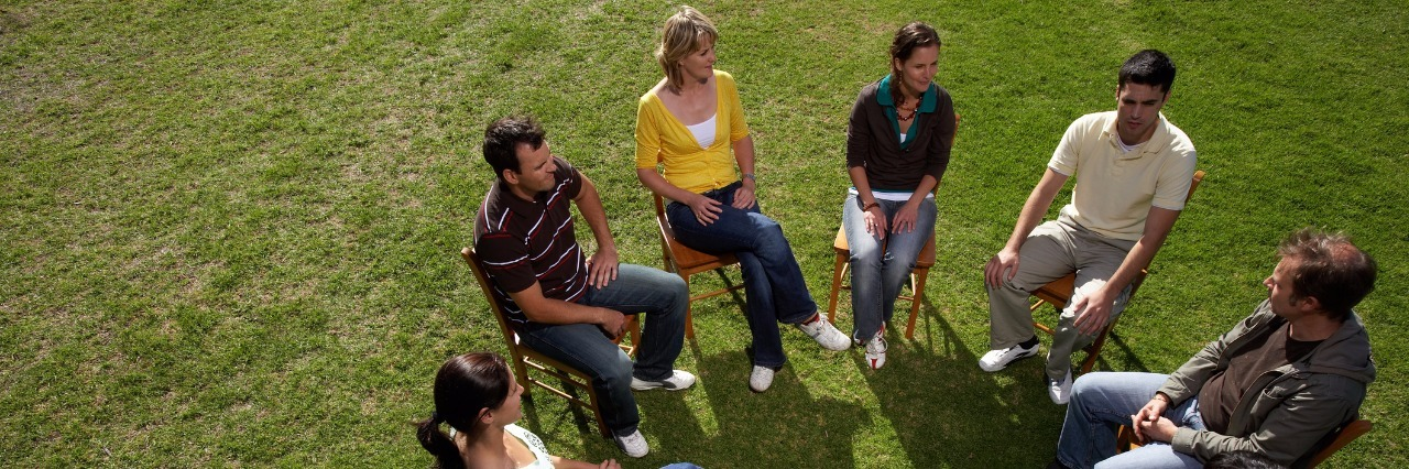 group of people sitting on chairs in a circle outside