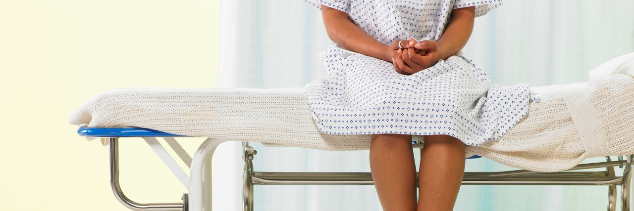 Female patient sitting on gurney in hospital gown