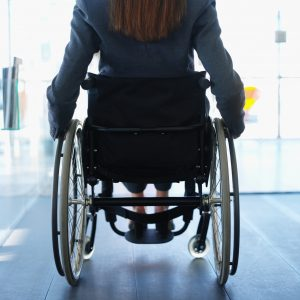 Woman sitting in a wheelchair in an office building.