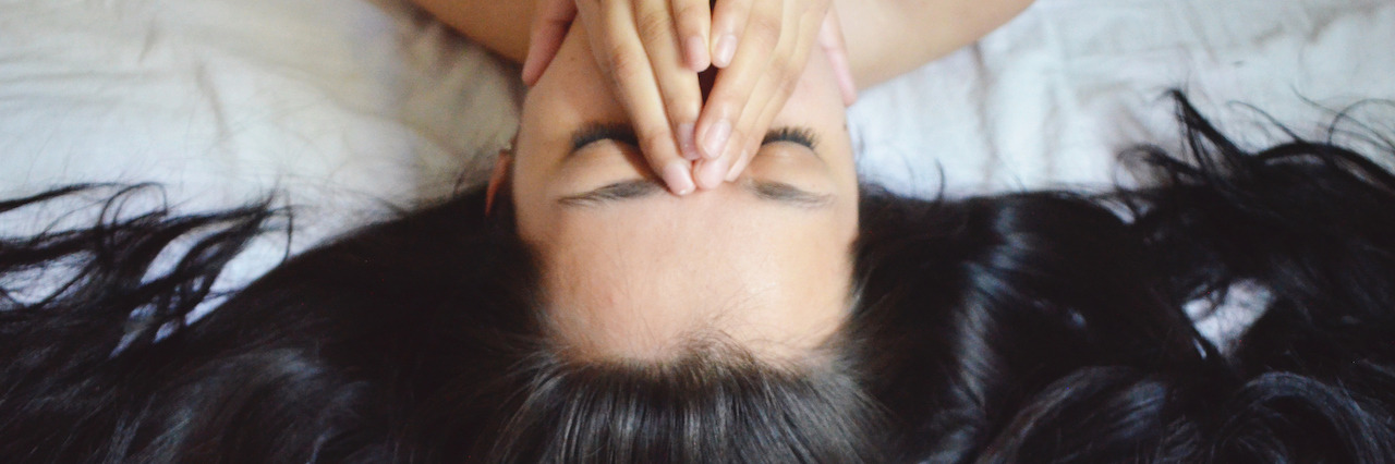 Woman lying on her bed with her hands covering half her face