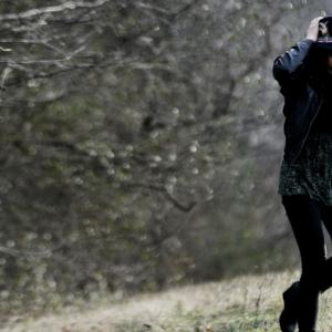 Woman wearing hat, walking near a tree in a field