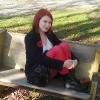 Emily O'Malley sitting on a bench. She has red hair and is wearing a white shirt, black jacket, bright red leggings and black boots.