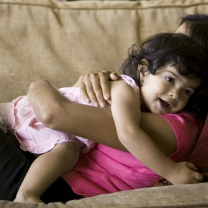 lifestyle shot of a mother as she lays on the couch and lovingly hugs her toddler daughter